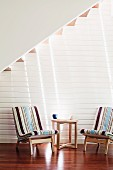 Easy chairs with striped upholstery and side table on dark parquet floor below staircase against white wooden wall