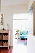 View through open sliding door into light-flooded room with sofa below window