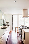 Parallel, white kitchen counters, extractor hood hanging from ceiling and glass, louvre terrace doors in background