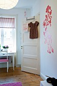 Child's bedroom with floral stickers on wall, dress on clothes hanger hanging on interior door