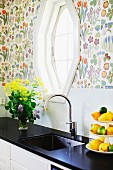 Modern kitchen counter with black worksurface and integrated sink below window in wall with colourful floral wallpaper