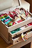 Paper gift tabs and colourful ribbons in small wooden case with open drawers