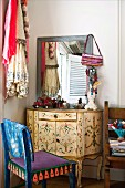 Vintage, Rococo-style dressing table and chair painted in ethnic patterns in corner of room