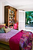 Patchwork bedspread on double bed, antique bookcase and open terrace doors with view of palm trees