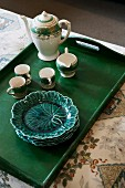 China tea set and cabbage-leaf plates on dark green wooden tray