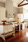 Large, open-plan country-house kitchen with wooden worksurfaces, white cabinets, white wood-clad ceiling and grey walls
