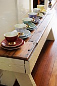 Espresso cups of various colours with gilt handles lined up on rustic wooden bench