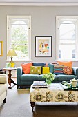 Colourful scatter cushions on blue sofa, side table and tray on ottoman in foreground