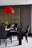 Black leather-covered chairs around solid-wood dining table below red pendant lamp and in front of rattan wall hanging on dark wall in elegant dining room