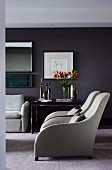 Extravagant armchairs with grey covers in elegant living room with dark-painted walls