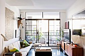 Modern and ethnic art above simple sofa and retro sideboard in front of industrial-style balcony door in living room