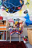 Soft toys on armchair and animal hopper below colourful painting in child's bedroom