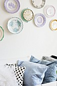 Row of plain and patterned scatter cushions below collection of plates and retro clock on wall