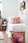 Pink plastic bag and craft utensils in wooden crate in front of simple bed with white bedspread and scatter cushions in rustic room