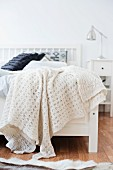 White, knitted blanket on white wooden bed in rustic room