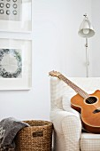 Guitar on armchair in front of retro standard lamp in corner