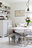 Dining area with table and chairs painted white in rustic interior with white wood walls and floor