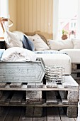Couch made from stacked wooden pallets and pale cushions in rustic interior
