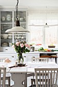 Nostalgic kitchen lamps above glass vase of roses on dining table in white, Swedish country-house kitchen