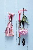 Old keys with ribbons and hand-crafted tassels made from fabric remnants hanging on pale blue wooden wall; peony stuck to wall with washi tape