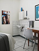 Grey plastic chair at table next to minimalist washing area in corner of bedroom with modern artworks on walls