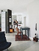 Vintage wooden chair at grey-painted table on Oriental rug in open-plan interior; woman in dining area in background