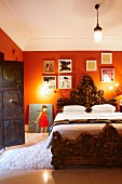 Magnificent bed with lavishly carved wooden frame, foot and headboard in traditional interior with deep orange walls