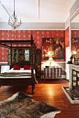 Traditionelles Himmelbett mit gedrechselten Holzsäulen, an Wand Ornament Tapete mit rotem Hintergrund in ländlich traditionellem Schlafzimmer