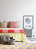 Scatter cushions in colourful mixture of graphic patterns on bed and rug with honeycomb pattern