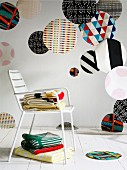 Various large colourful fabric circles of various patterns hanging in interior, stacked blankets on white metal chair and white wooden floor