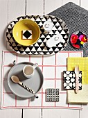 Crockery on grey tray and patterned tray on various table mats