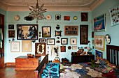Patchwork quilt on bed and gallery of artworks on turquoise-painted wall in artistic interior