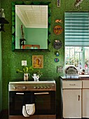 Modern stainless steel cooker and mirror on wall with green mosaic tiles; vintage sink unit with base cabinet to one side below window