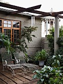 Delicate wire mesh sun loungers under pergola on terrace adjoining grey-painted house with wooden windows
