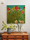 Blumen in Vasen und Kerzenständer mit weissen Stumpenkerzen auf Holzkommode vor Wand mit gemaltem Blumenbild