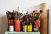 Painter's utensils - various containers of paintbrushes on cabinet next to rolls of paper