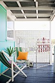 Chill-out zone - striped deckchairs on dark wooden floor of veranda with white lattice wooden screen