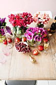Vases of flowers and fruit on simple wooden table