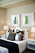 Modernes Schlafzimmer mit Doppelbett, Dekokissen, Nachtkästchen mit Lampen und Wandbildern