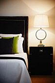Stylish bedroom with designer lamp on bedside cabinet