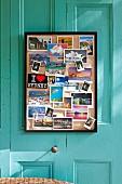 Gerahmte Pinnwand mit verschiedenen Ansichtskarten an türkisfarbener Kassettenverkleidung einer Vintage Veranda