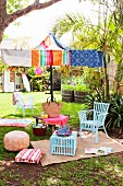 Casual picnic atmosphere in summery garden with colourful beach towels as parasol