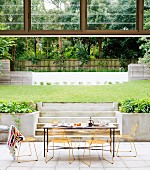 Breakfast table in seating area on terrace of architect-designed house with modern garden pool in background