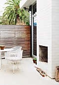 Open fireplace in white, outdoor chimney breast of Australian beach house with terrace and screen fence of narrow wooden slats