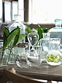 Arrangement of various glass vessels on wooden table in elegant country-house style