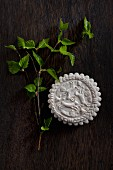 Aniseed biscuit with moulded hare motif and young birch twig on wooden table