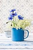 Elderflowers and cornflowers in small, blue enamel pot