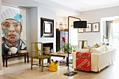 Eclectic interior with black retro standard lamp, white, loose-covered sofa, green wooden chairs and large portrait on wall
