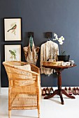 Pale bamboo chair an antique side table against black-painted wall with framed pictures of birds & coat hooks