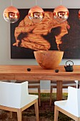 Spherical, copper pendant lamps above wooden bowl on table and chairs with white backrests and arms